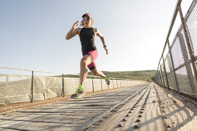 Спортсмен, біг і стрибки на мосту — стокове фото