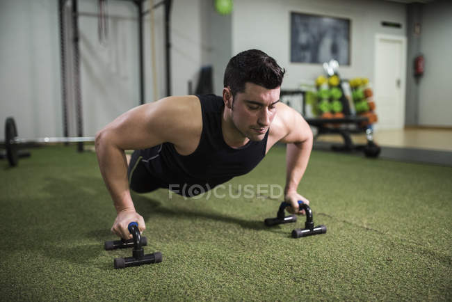 Young crossfit athlete doing pushups in gym — Stock Photo