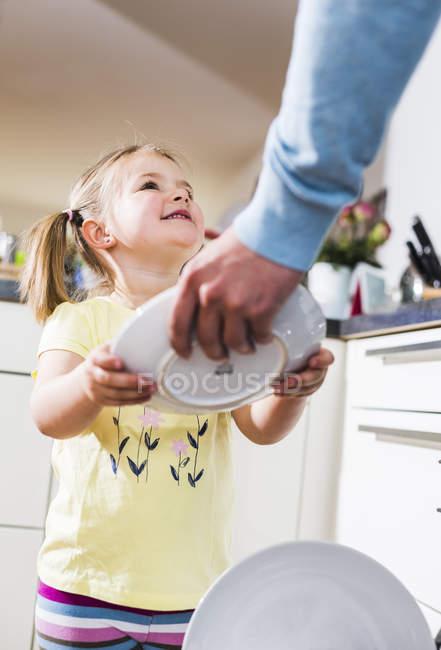 Hija ayudando a padre a limpiar lavavajillas - foto de stock