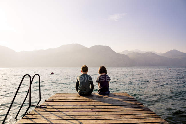 Back view brother and sister sitting side by side on jetty — Stock Photo