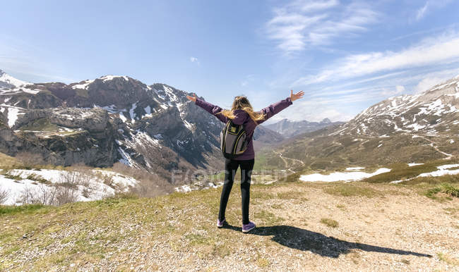 Woman standing with raised arms in mountains — Stock Photo