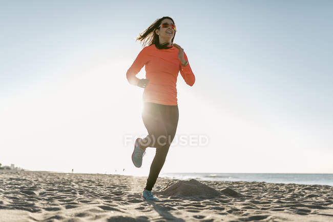 Frau in den frühen Morgenstunden am Strand joggen — Stockfoto