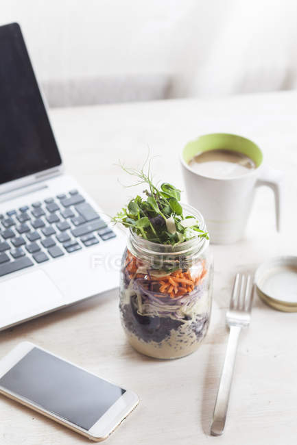 Rainbow salad in jar with smartphone, mug of coffee and laptop — Stock Photo