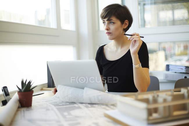 Architecte assis au bureau regardant par la fenêtre — Photo de stock