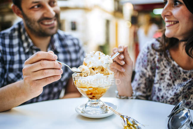 Couple eating ice cream in a street cafe — Stock Photo