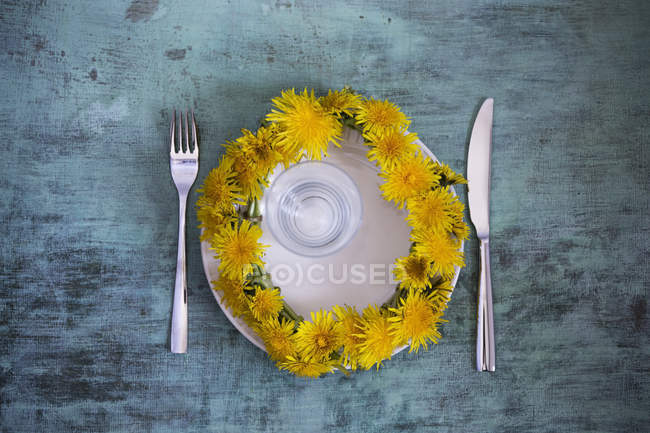 Wreath of dandelions on plate over wooden surface — Stock Photo