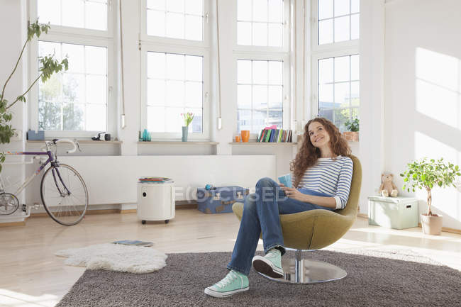 Relaxed woman at home sitting in chair — Stock Photo
