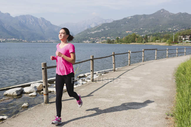 Italy, Lecco, young woman running along the lake — Stock Photo