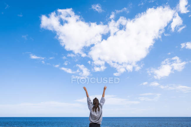Young woman reaching with arms to the sky — Stock Photo