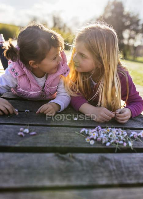 Kleine Mädchen legen sich mit Gänseblümchen auf die Promenade und schauen einander an — Stockfoto