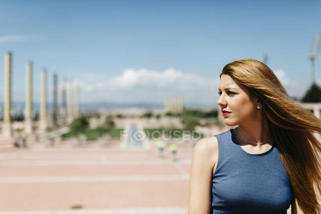 Spain, Barcelona, woman with blowing hair watching something — Stock Photo