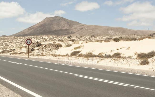 Espagne, Fuerteventura, Corralejo, Parque naturel de Corralejo, vue du chemin vide et panneau de signalisation — Photo de stock