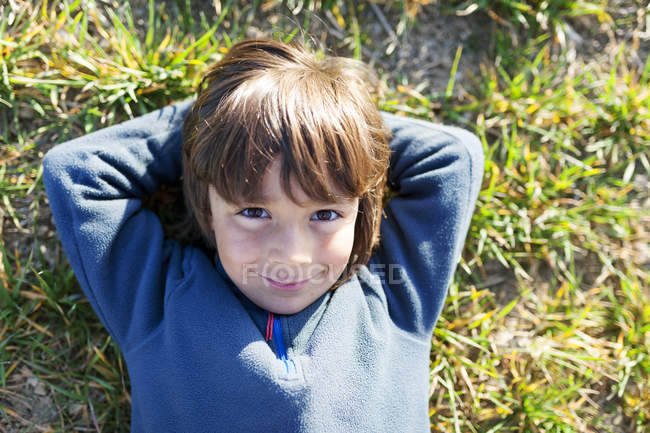 Portrait of smiling boy sitting in meadow — Stock Photo