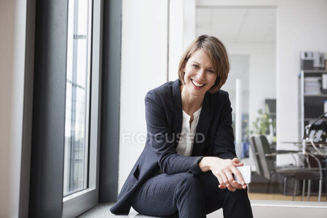 Smiling businesswoman sitting at window and looking at camera — Stock Photo