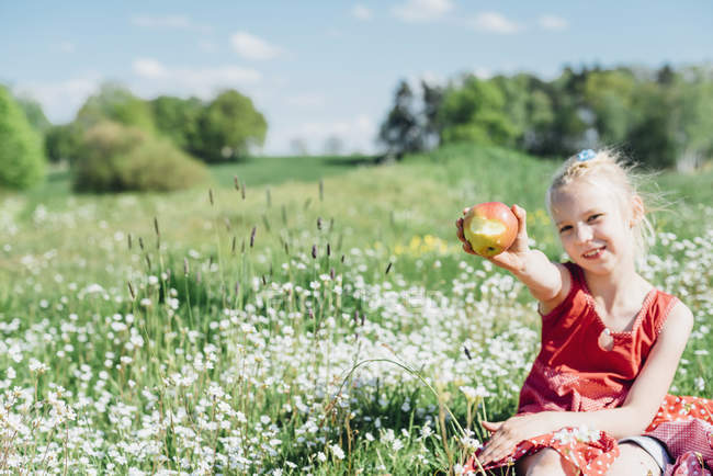 Девушка, сидящая на лугу — стоковое фото