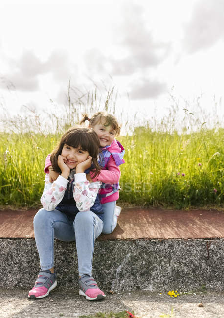 Portrait of two little sisters sitting on pavement in front of a meadow — Stock Photo