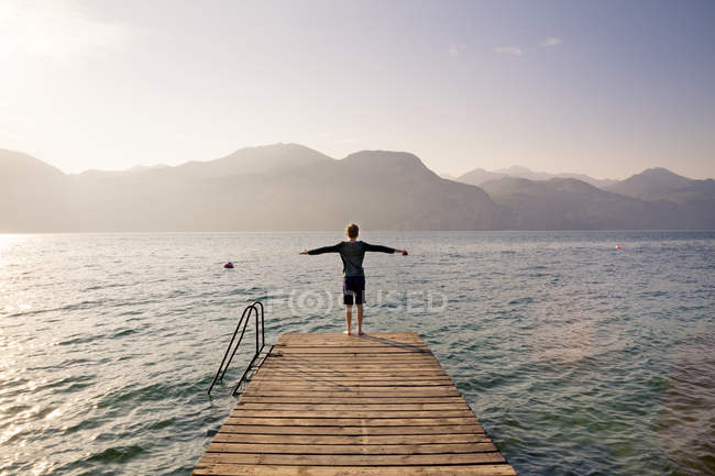 Back view of boy standing on jetty with arms outstretched — Stock Photo