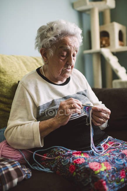 Portrait of crocheting senior woman sitting on couch at home — Stock Photo