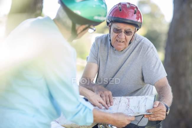 Літня пара з картою на велосипедах — стокове фото