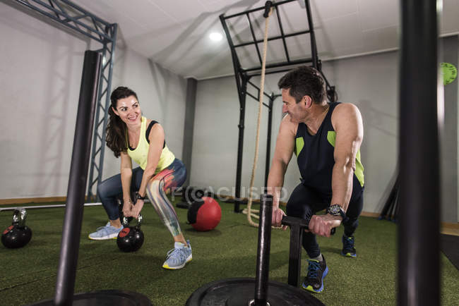 Mature couple training with kettlebell and sled weights in crossfit circuit — Stock Photo