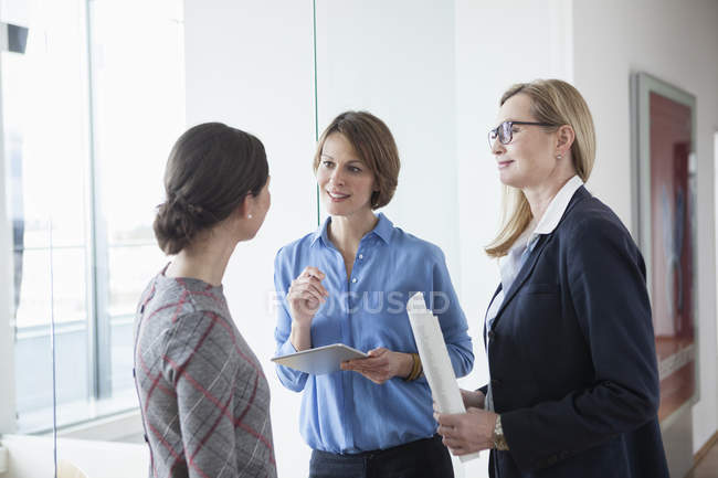 Three businesswomen discussing in modern office — Stock Photo