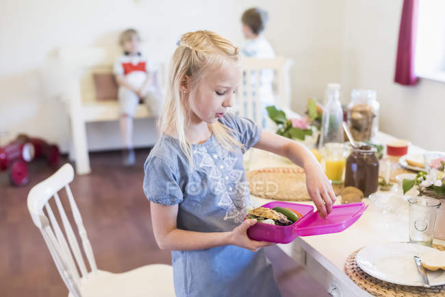 Girl packing lunch box — Stock Photo