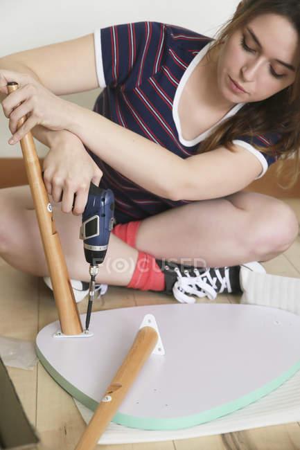 Frau montiert Flatpack-Möbel mit Elektro-Schraubenzieher — Stockfoto