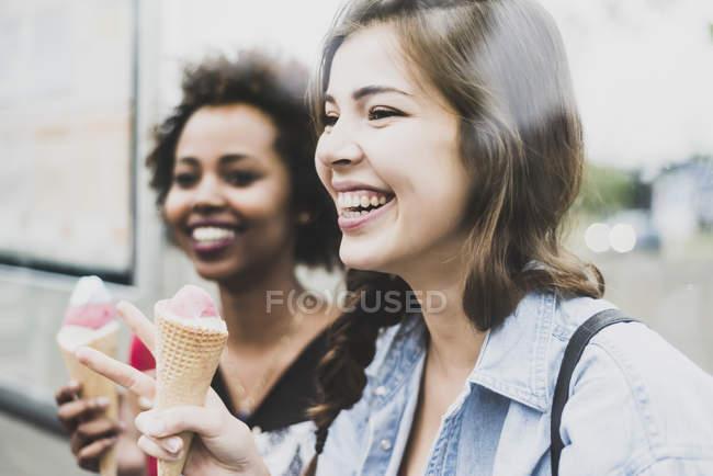 Rindo mulher com cone de gelado e amigo no fundo — Fotografia de Stock