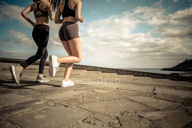Кадроване зображення двох подруг, працює на березі океану — стокове фото