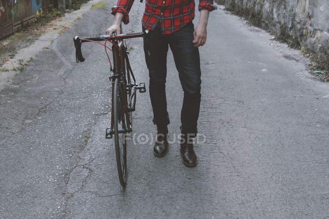Человек с гоночным велосипедом ходит по улице — стоковое фото