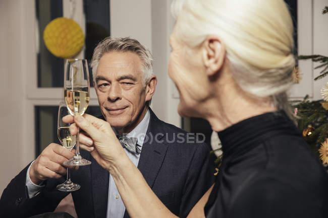 Старшие пары звонят в бокалы с шампанским в канун Нового года — стоковое фото