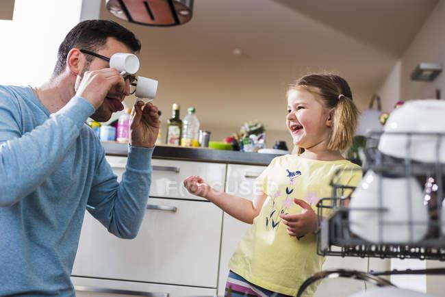 Игривая дочь и отец чистят посудомоечную машину — стоковое фото