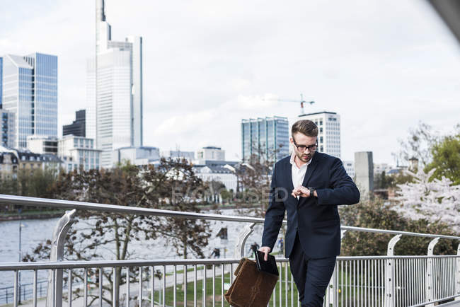 Young businessman walking in the city, checking time — Stock Photo
