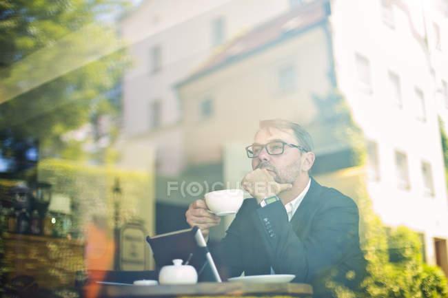 Бизнесмен с чашкой кофе сидит в кафе — стоковое фото