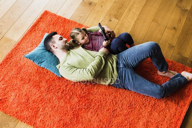 Padre e figlia che si trova sul tappeto sul pavimento per mezzo della compressa di digital — Foto stock