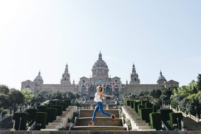 Spain, Barcelona, Young woman on sightseeing tour in front of museum — Stock Photo
