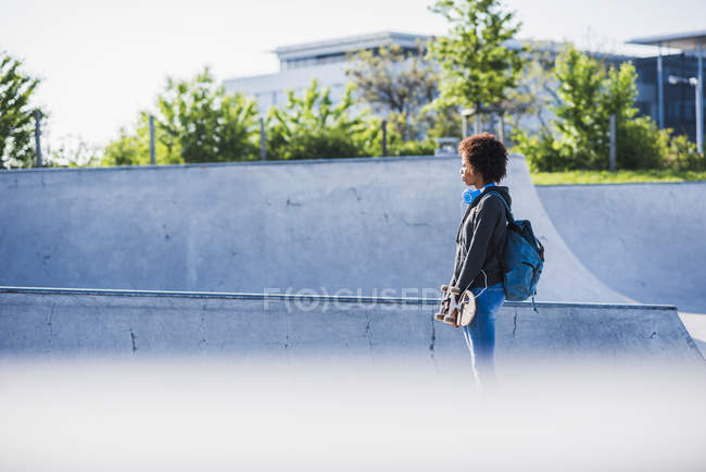 Young woman with skateboard in skatepark — Stock Photo