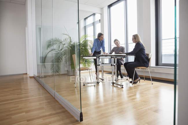 Foto Ufficio Moderno : Tre donne di affari che ha riunione in ufficio moderno u2014 foto stock