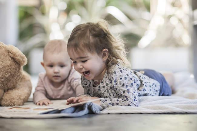 Duas garotas de bebê deitado sobre um cobertor no chão a olhar para o livro — Fotografia de Stock