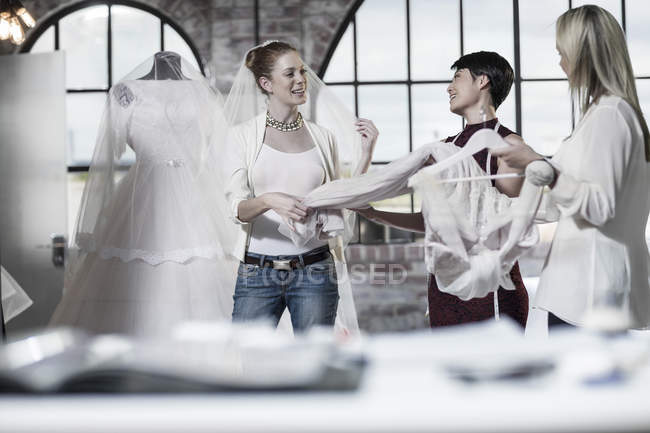 Wedding dress designers and bride to be working in bridal store — Stock Photo