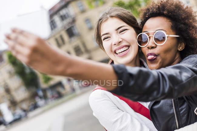 Ritratto di due migliori amici felici che scattano selfie con smartphone — Foto stock