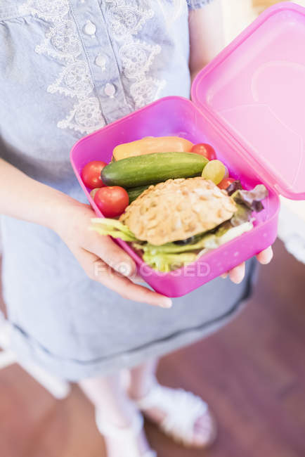 Girl holding lunch box with healthy food — Stock Photo