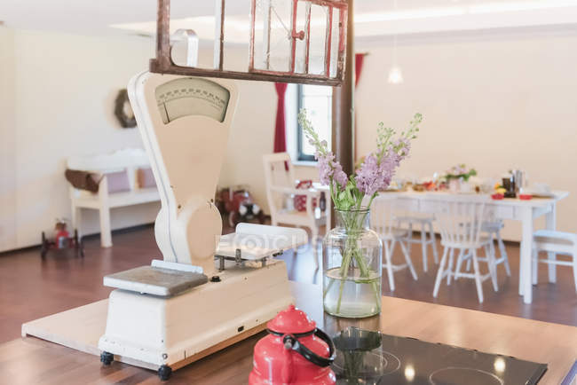 Flowers and vintage kitchen scales on kitchen island — Stock Photo