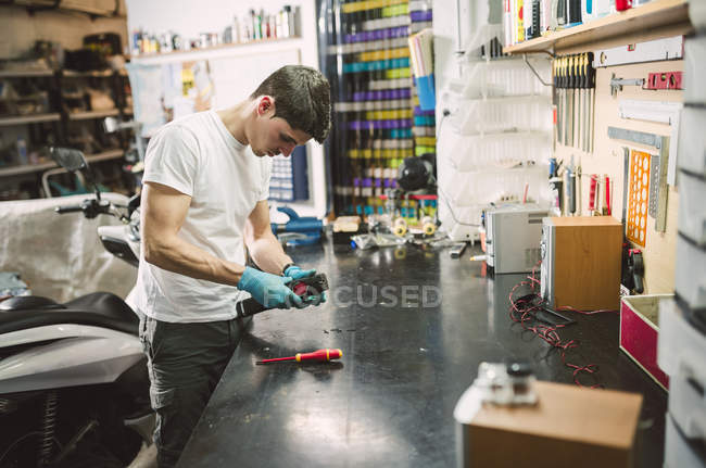 Electronic technician fixing an electronic device at workbench — Stock Photo