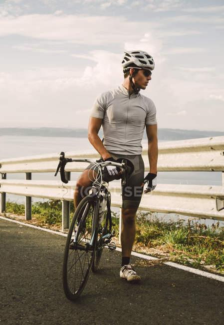 Велогонщик с гоночным велосипедом стоит на дороге у берега — стоковое фото
