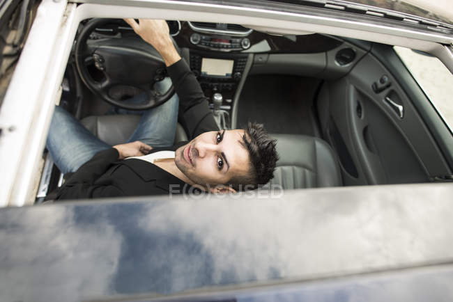 Young man sitting in car with open sunroof — Stock Photo