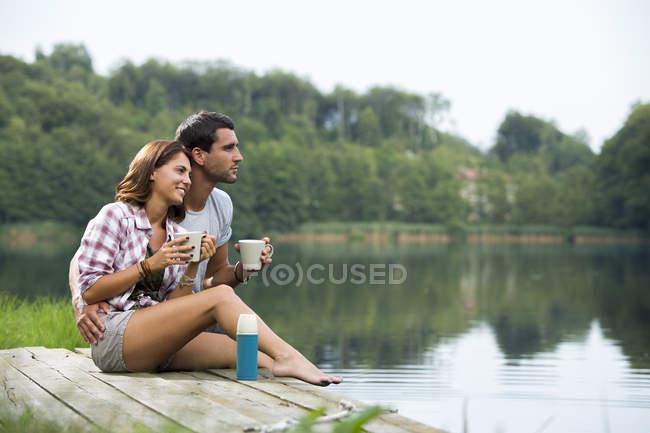 Pareja joven relajado con tazas de café, sentado en un muelle en el lago buscando a distancia - foto de stock