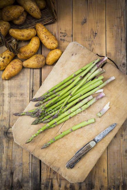 Espargos verdes e faca na placa de desbastamento — Fotografia de Stock