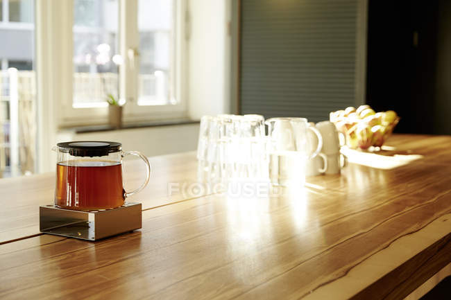 Teapot on teapot warmer on tabletop in a modern office — Stock Photo