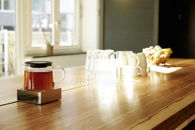 Teekanne auf Stövchen auf Tischplatte in einem modernen Büro — Stockfoto